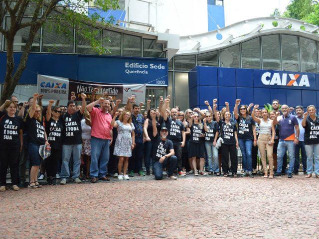 De preto, empregados da Caixa protestam contra reestruturação